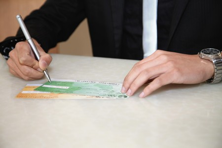 signing authority: Businessman signing cheque with pen