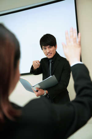 Businessman pointing at businesswoman who is raising her hand photo