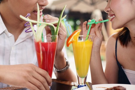 drinking straw: Man and woman enjoying their drinks Stock Photo