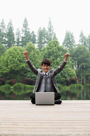 Businessman sitting in front of laptop and raising his hands photo