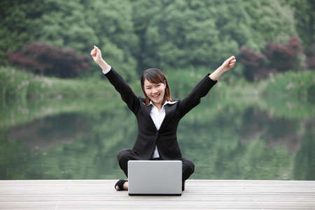 Businesswoman sitting in front of laptop and raising her hands photo