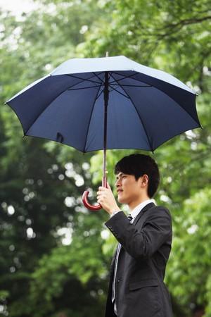Businessman holding an umbrella Stock Photo - 7839331
