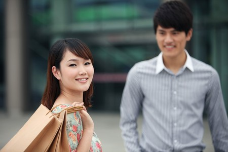 man and woman with shopping bags: Woman with shopping bags, man in the background Stock Photo