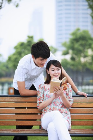 Woman sitting on bench reading book, man watching from behind photo
