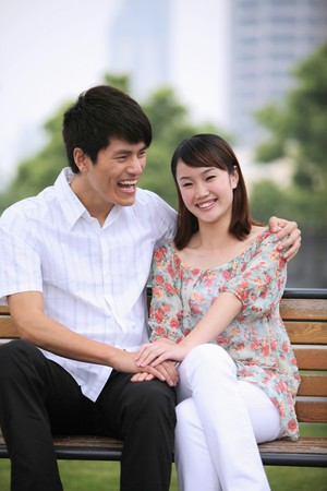 Man and woman sitting on a bench, smiling Stock Photo - 7839334