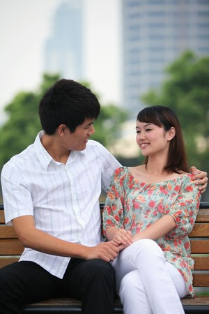 Man and woman sitting on a bench, smiling photo