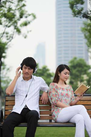 Man listening to music on the headphones, woman reading book on the bench photo