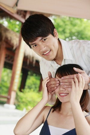 Man covering womans eyes with hands photo