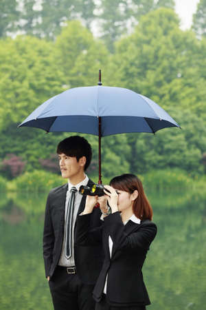 Businesswoman looking through binoculars, businessman shielding her with an umbrella photo