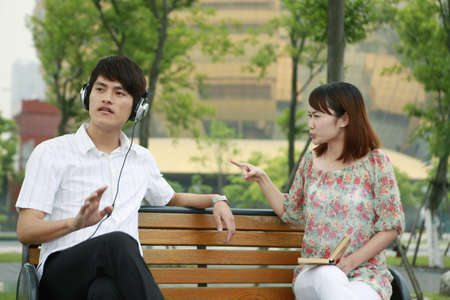 nagging: Man listening to music on the headphones, woman scolding man