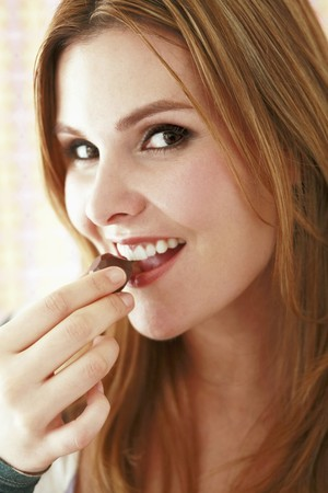 Woman eating chocolates photo