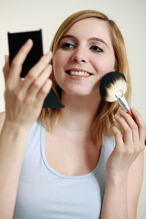 Woman applying blusher on her cheeks photo