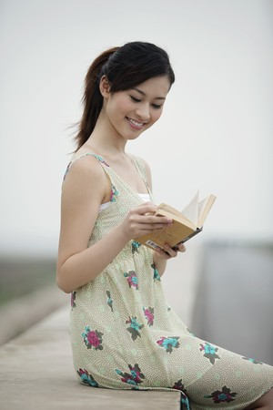 Woman reading book outdoors photo
