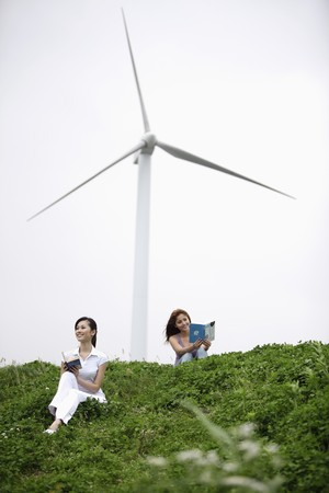 leis: Women reading outdoors with wind mill in the background