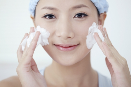 cleanse: Woman cleansing her face Stock Photo