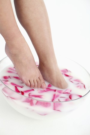 Woman soaking feet in bowl of milk and rose petals photo