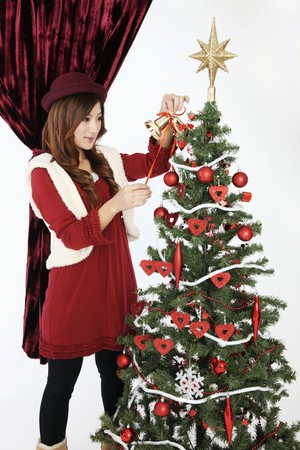 Woman decorating Christmas tree Stock Photo - 8149427