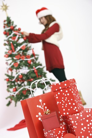 Gift boxes and shopping bags with woman decorating Christmas tree in the background photo