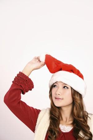 Woman lifting Santa hat photo