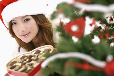 Woman holding heart-shaped chocolate box peering from behind Christmas tree photo