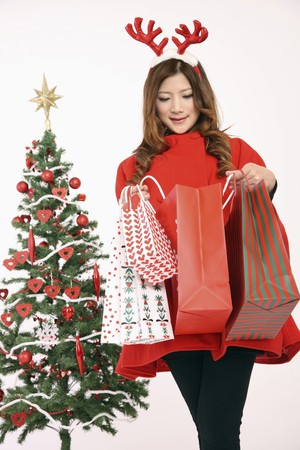 Woman wearing reindeer antler holding shopping bags photo