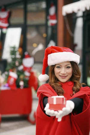 Woman wearing Santa hat showing gift box in hand photo