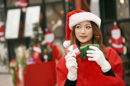 wearing santa hat: Woman wearing Santa hat holding gift box and Christmas stocking