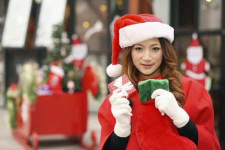 Woman wearing Santa hat holding gift box and Christmas stocking photo