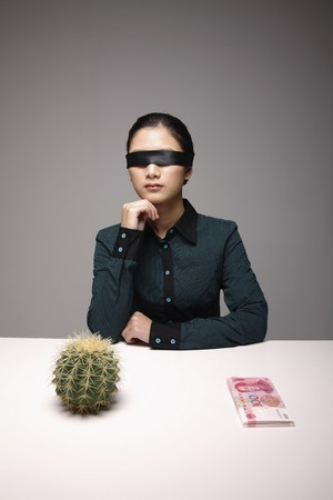 Woman with blindfold contemplating photo