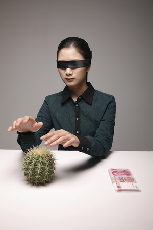 Woman blindfolded with hands above cacti photo