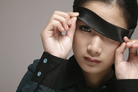 Woman lifting up blindfold photo