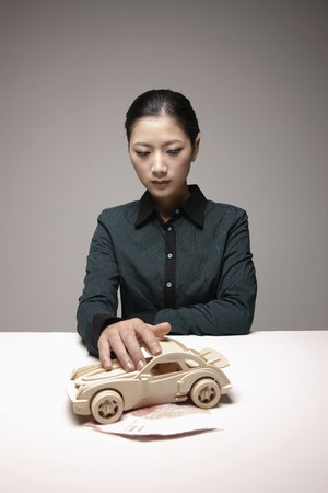 Woman with hand on toy car photo