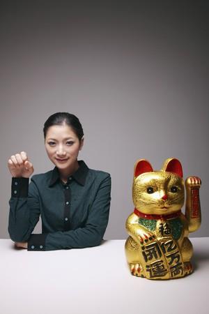 imitating: Woman imitating ceramic cat ornament