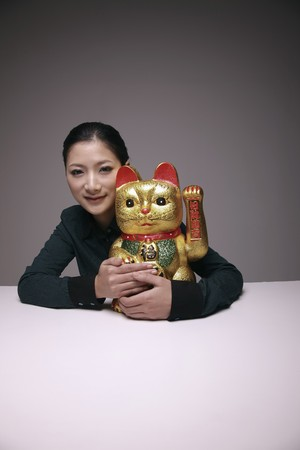 Woman hugging ceramic cat ornament Stock Photo - 8148690
