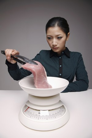 Woman holding a piece of meat with tongs and putting it on a scale photo