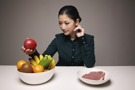 Woman holding an apple from a bowl of fruits Stock Photo - 8148847