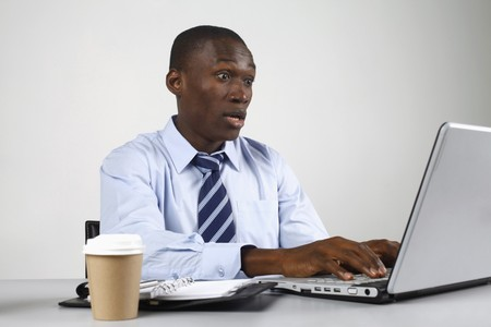 Businessman in shock while using laptop photo