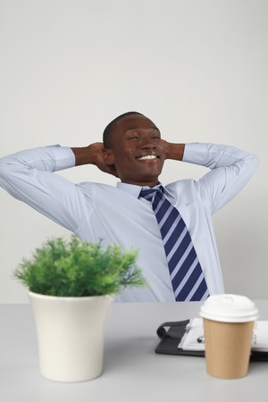 Businessman resting with hands behind head photo