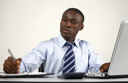 Businessman writing on organizer while using laptop photo
