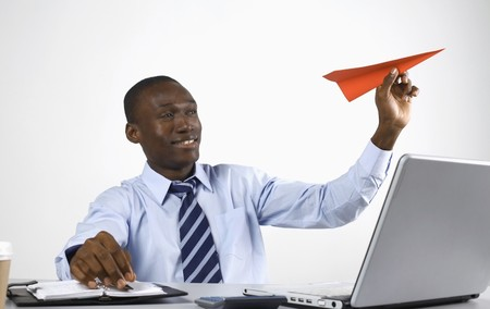 Businessman playing with paper airplane photo