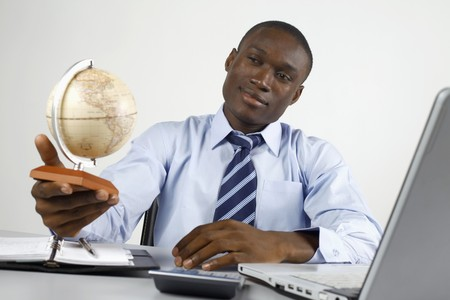 Businessman thinking while looking at globe photo