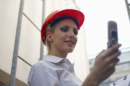 belarusian ethnicity: Female architect reading messages on her mobile phone