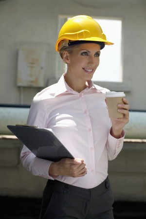 belarusian ethnicity: Female architect holding a cup of coffee and clipboard