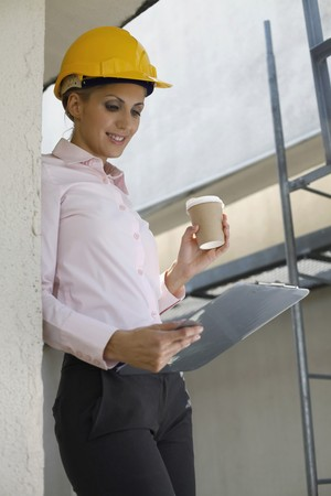 Female architect holding a cup of coffee and clipboard photo