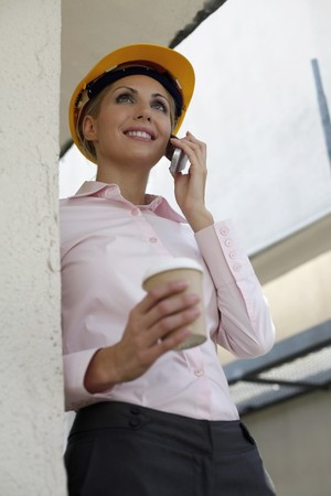 belarusian ethnicity: Female architect holding a cup of coffee while talking on the phone Stock Photo