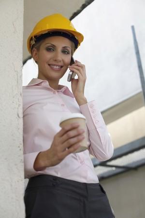 belarusian ethnicity: Arquitecto mujer sosteniendo una taza de caf� mientras habla por tel�fono