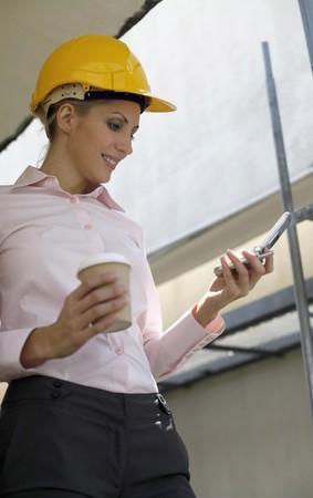 belarusian ethnicity: Arquitecto de mujer sosteniendo una taza de caf� mientras los mensajes en el tel�fono de texto  Foto de archivo
