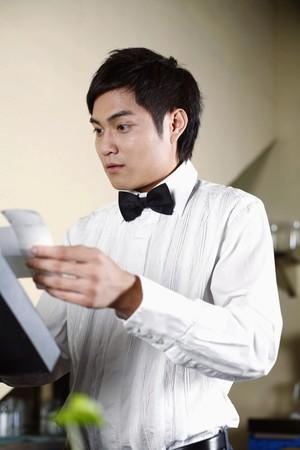 Waiter at checkout counter photo