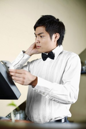Waiter at checkout counter Stock Photo - 8148086