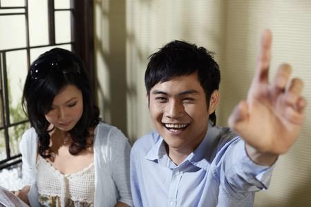 Man gesturing to order food, woman reading menu photo